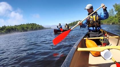 Deux canots sur le lac avec trois personnes qui pagaient