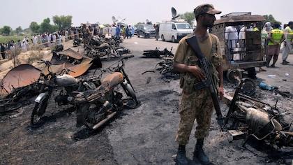 Un soldat posté près des carcasses calcinées de motos renversées sur la route