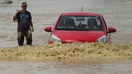 Un homme et une voiture circulent difficilement dans une rue inondée de Porto Rico après le passage de l'ouragan Maria.