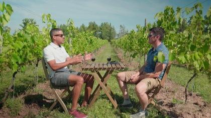 Franz Bergevin-Jean et Samuel Chiasson assis à une table bistro au centre de la rangée d'un vignoble.