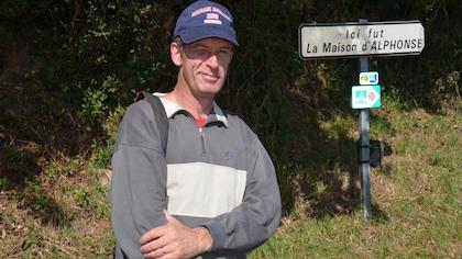 """Un homme se tient devant un panneau où il est inscrit """"Ici fut la Maison d'Alphonse""""."""