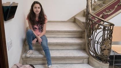 La jeune fille est assise sur une marche d'escalier en marbre. Elle porte un jeans et un t-shirt rose qui affiche un dessin.