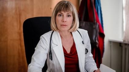 Une infirmière à son bureau. Elle porte une blouse de travail et a un stéthoscope autour du cou.