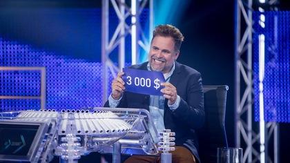 Il sourit à pleine dents et tient un carton avec la mention 3000$.