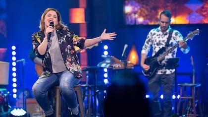 La comédienne chante sur scène, assise sur un tabouret. Un musicien est derrière elle.