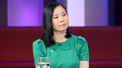 Cathy Wong porte une robe verte.