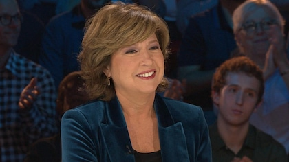 La journaliste sur  le plateau des enfants de la télé. Elle porte un veston bleu et sourire.