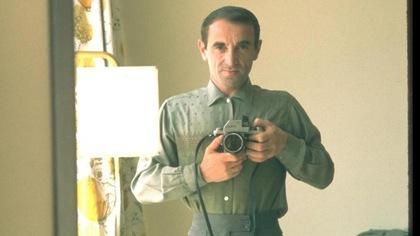 Le chanteur est très jeune. Il tient un appareil photo devant un miroir.