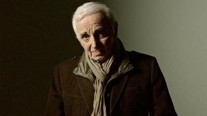 Il porte un manteau brun et un foulard beige.