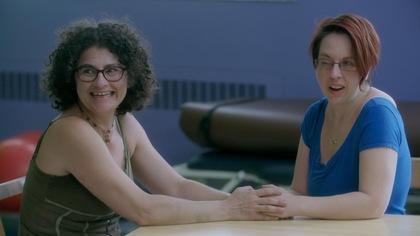 Les deux femmes sont assises à table et se tiennent les mains en riant.