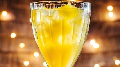 Le cocktail est servi dans un verre sur pied qui contient des glaçons