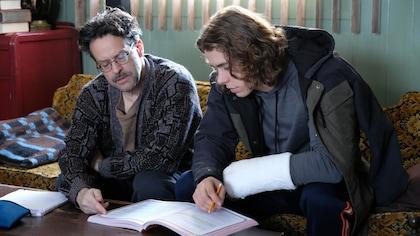 Les deux comédiens lient un manuel scolaire ouvert sur une table.