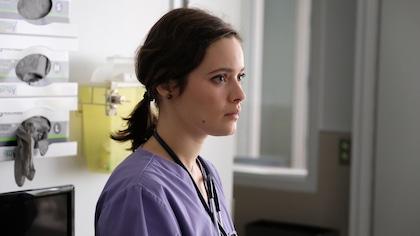 La comédienne Marianne Fortier est vêtue d'un habit d'infirmière et regarde au loin.