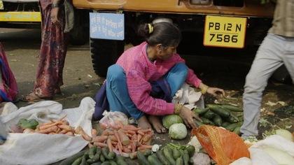 Une femme étend des légumes par terre.