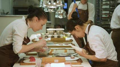 Deux femmes préparent des assiettes de nourriture avec minutie.