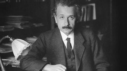 Une photo en noir et blanc. Einstein porte une chemise blanche, une cravate,un gilet et un habit. Il est assis à son bureau.