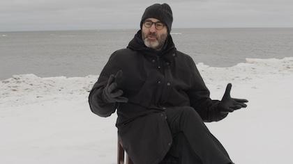 Un homme assis dehors. Sa chaise est posée sur la neige. Derrière lui, on voit la mer.