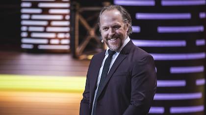 En veston cravate, il fait un sourire moqueur sur scène.