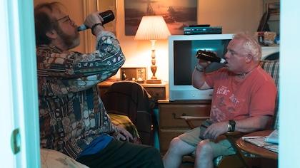 Ils sont assis l'un en face de l'autre et ils boivent de la bière.