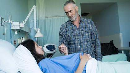 Une jeune femme enceinte est couchée dans un lit d'hôpital. Un homme, debout à côté du lit, lui tient la main.