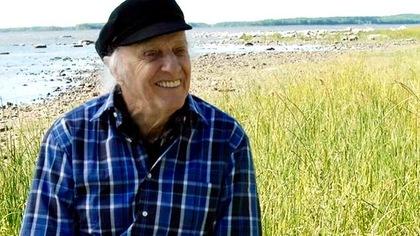 Gilles Vigneault, souriant, au bord du fleuve, portant une chemise à carreaux et une casquette