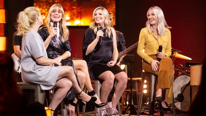 Quatre femmes blondes assises sur des tabourets sur scène.