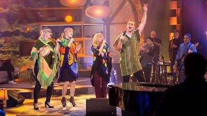 Ils chantent sur scène vêtus de ponchos colorés.