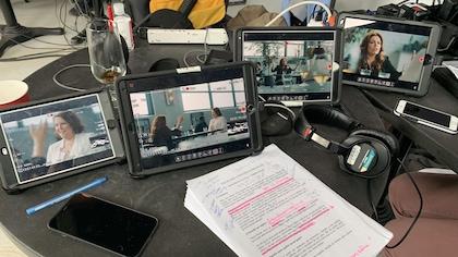 Des écrans, téléphones, écouteurs et papiers sur une table.