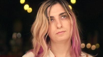Une femme aux cheveux blonds traversés de mèches roses.