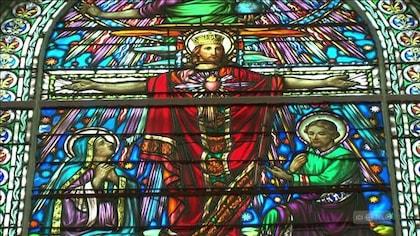 Jésus sur la croix est représenté sur un vitrail coloré, Marie et Joseph sont installés à ses pieds.