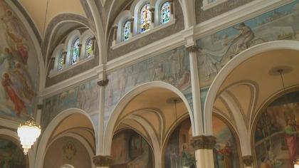 Vue du plafon de l'intérieur d'un oratoire, avec ses vitraux colorés et ses fresques religieuses.