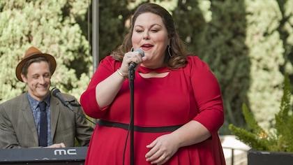 Elle porte une robe rouge. Elle chante, accompagnée d'un claviériste.