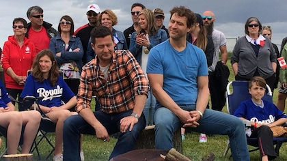 Kevin Parent et Dany Turcotte sont assis sur un rondin et sont entourés des habitants de Charlottetown.