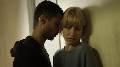Un homme et une femme sont accolés sur un mur.