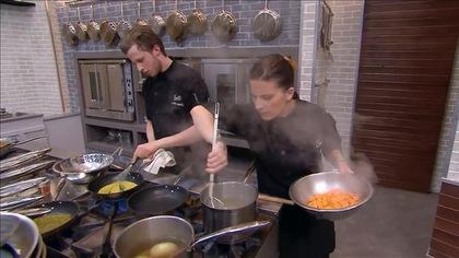 Marc-Antoine brasse une sauce dans une poêle et Ashley sort des aliments d'un chaudron.