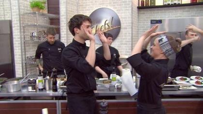 Deux aspirants chefs, se tappent dans les mains dans la cuisine.