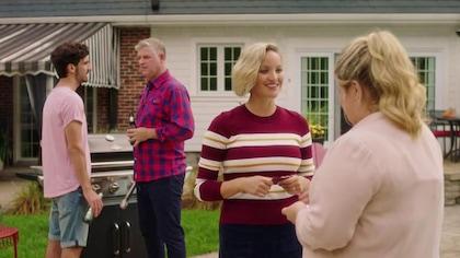 Deux femmes discutent affaires pendant que deux hommes jasent, bière à la main, à côté du barbecue.