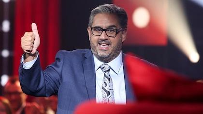 Marc Hervieux a le pouce en l'air. Il porte un complet cravate et des lunettes.
