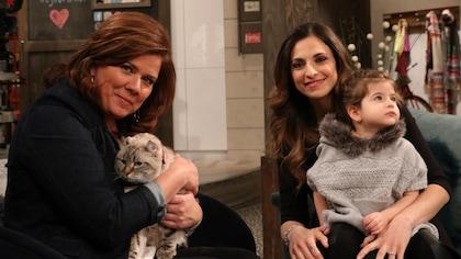 Marina Orsini tient un chat dans ses bras et la vétérinaire tient sa fille sur ses genoux.