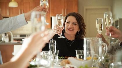 Claire est à table avec plusieurs personnes et lève son verre.