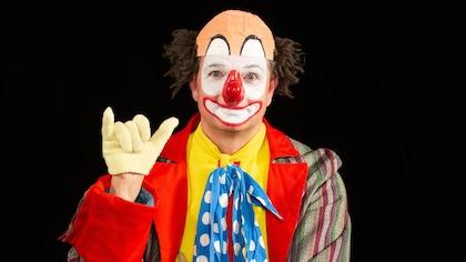 Un clown avec un nez rouge, une chemise jaune, une cravate bleue à pois blancs, des pantalons rouges et un veston à rayures colorées.