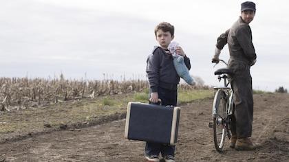 Olivier tient sa valise et son ourse en peluche.