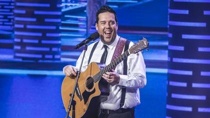 Il tient une guitare en riant sur scène.