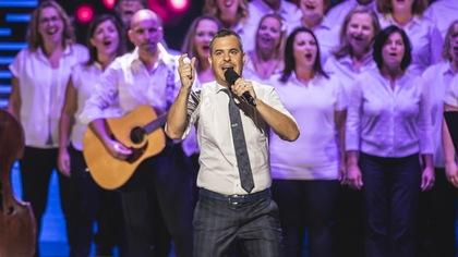 Il chante sur scène avec une chorale.