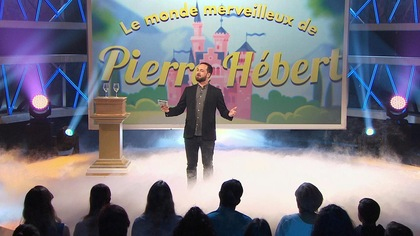Il est sur scène et derrière lui un décor magique avec un château où on peut lire Le monde merveilleux de Pierre Hébert.