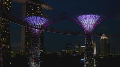 Des gens sur une passerelle dans une ville illuminée le soir.