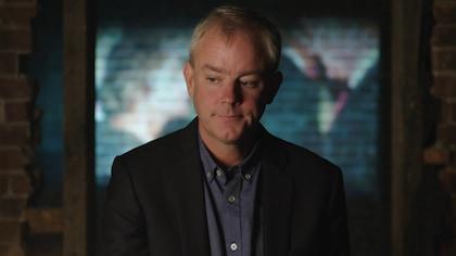 Un homme qui porte une chemise bleue et un veston noir.