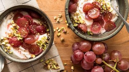 Des bols de yogourt parsemés de raisins coupés en deux et de miettes de pistaches.