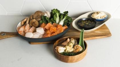 Trois différents plats contiennent des garnitures pour la fondue de la sauce et une soupe won ton.