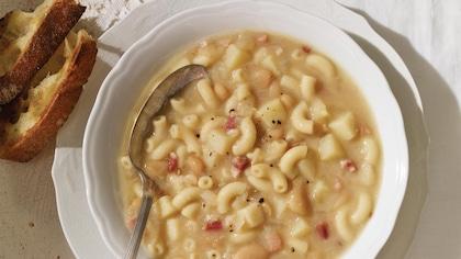 Un bol de soupe avec des macaronis et des lardons, dans lequel on a déposé une cuillère.